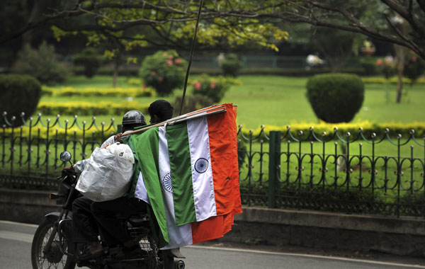 An Indian street vendor sitting as a pillion on a motorcycle holds national flags for sale at a busy intersection in Bangalore. (AFP)