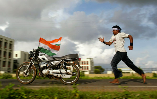 Ekan, 30, chases his bike adorned with Indian national flags as he practices stunts at the Bhuabneswar-Puri national highway ahead of the dare devil show. (AP)