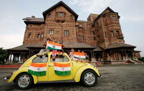 Children hold Indian national flags as they sit on a car during a photo-shoot in front of Hari Palace during the Independence Day celebrations in Jammu August. (REUTERS)