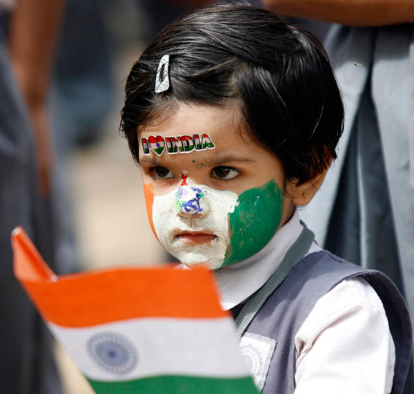A schoolgirl, with her face painted in colours of the Indian national flag, holds a flag during Independent Day celebrations inside her school in the western Indian city of Ahmedabad. (REUTERS)