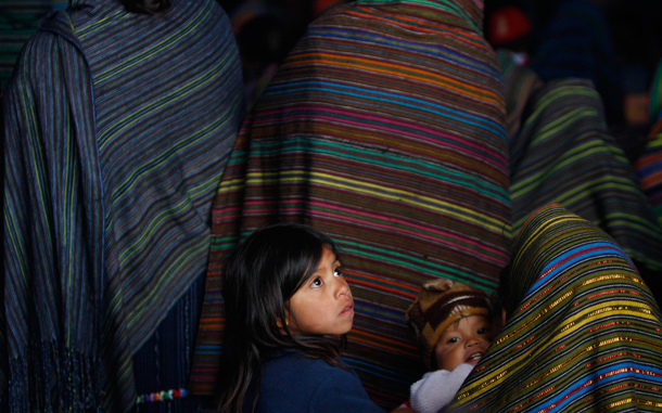 Quiche indigenous children sit with their parents at a funeral mass for mudslide victims in Santa Maria Ixtahuacan, Guatemala. Torrential rains from a tropical depression caused landslides that have killed at least 38 people in Guatemala. (AP)