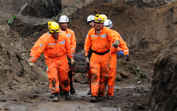 Rescue workers carry a landslide victim on a stretcher in La Cumbre de Alaska. As many as 100 people may have been buried in a landslide in Guatemala on a major highway, a spokesman for the fire department said on Sunday. Approximately 100 people were attempting to dig a bus out of a first mudslide when a second engulfed the scene, said fire department spokesman Sergio Vasquez. (REUTERS)