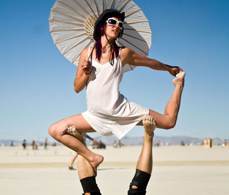 Participants perform a routine of strength and endurance Wednesday afternoon on the open playa during Burning Man 2010 in Black Rock City. (AP)