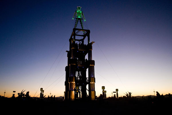 Man stands tall as the sun sets on Black Rock City, Nev. during Burning Man 2010. For one week out of the year, a portion of the Black Rock Desert is transformed into a thriving diverse city known as Black Rock City. (AP)
