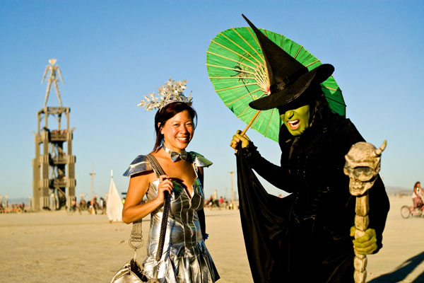 Burners show off their costumes as the man keeps watch in the distance during Burning Man 2010 in Black Rock City, Nev. (AP)