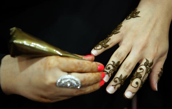 An Emirati woman paints henn on the hand of a visitor at the Abu Dhabi International Hunting and Equestrian exhibtion. (AFP)