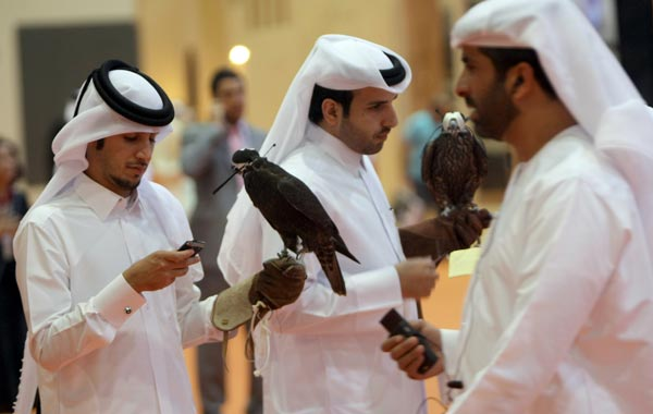 Qatari men hold their newly-purchased falcons at the Abu Dhabi International Hunting and Equestrian exhibtion (ADIHEX). (AFP)