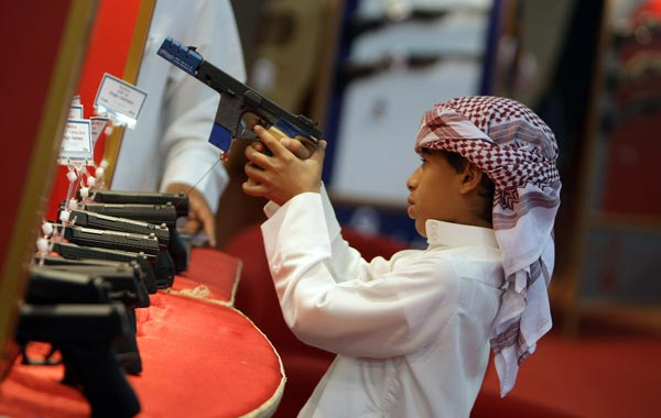 A young boy looks at a gun on display on the first day of the Abu Dhabi International Hunting and Equestrian exhibtion (ADIHEX). (AFP)
