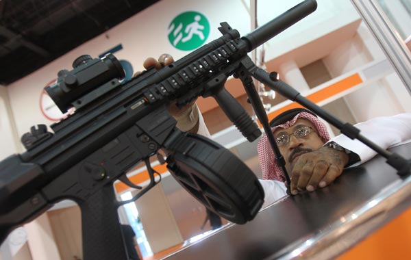 An Emirati man checks a gun on display on the first day of the Abu Dhabi International Hunting and Equestrian exhibtion (ADIHEX). (AFP)