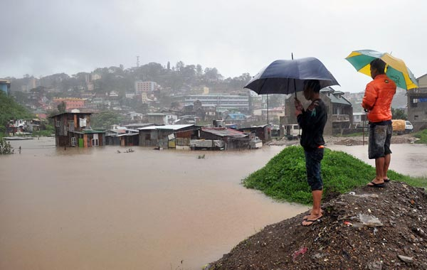 Residents stand as rain continues to lash down on their homes submerged by flooding due to Typhoon Megi in Baguio City, Benguet province, north of Manila. (AFP)