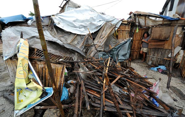 A woman surveys her house, destroyed by the strong winds of typhoon Megi in a slum area in Manila Bay. (AFP)
