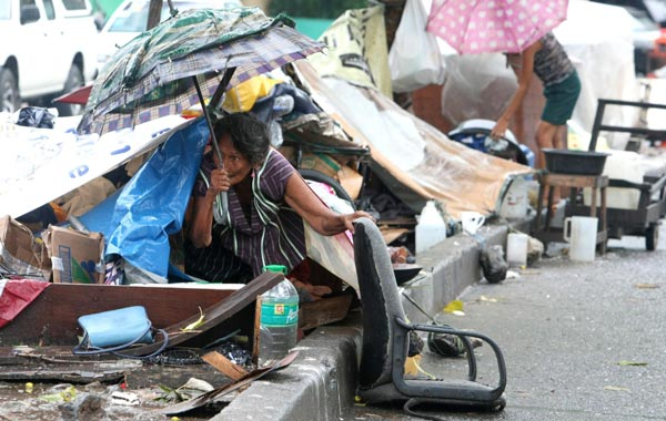 Filipinos seek refuge against the rain on makeshift shelter along the sidewalk in Quezon city East suburban Manila, Philippines. (EPA)