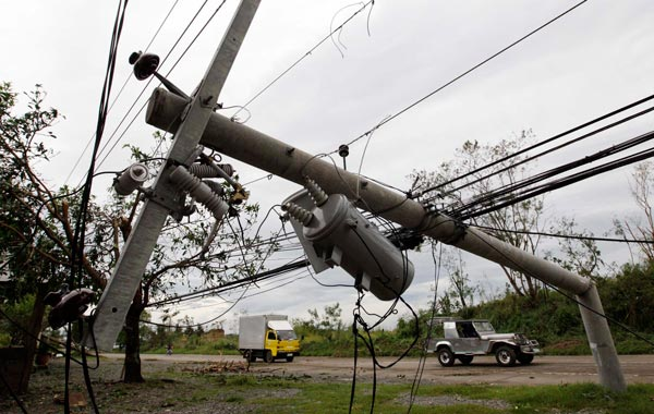 Filipino motorists drive past damaged electric post  after the onslaught of  Typhoon Megi in Cauayan town, Isabela province, northern Philippines. (EPA)