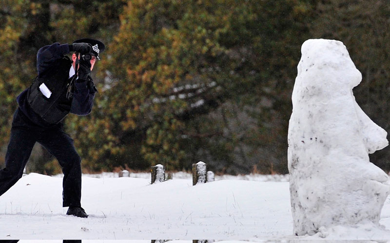 A Parks Police officer takes photographs of a snowman in Richmond Park in south west London December 1, 2010. The snow and freezing temperatures continued to cause major problems for road, rail and air services on Wednesday.  (REUTERS)