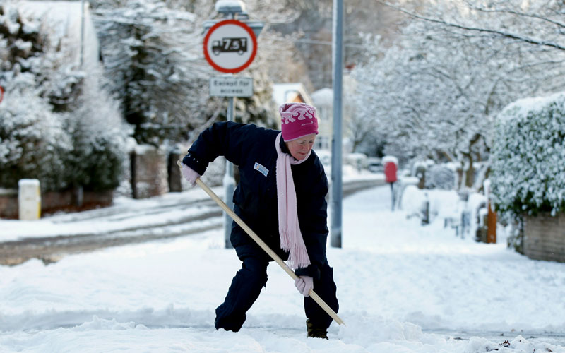 A woman clears snow outside her home on November 30, 2010 in Macclesfield, United Kingdom. The peak district town of Buxton in Derbyshire remains virtually cut off  by overnight snow fall as freezing weather conditions and snow has created chaos in Scotland and Northern England and is now moving south to the capital.  (GETTY IMAGES)