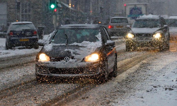 Cars drive slowly along a road during snow fall in Edinburgh, Scotland. (REUTERS)