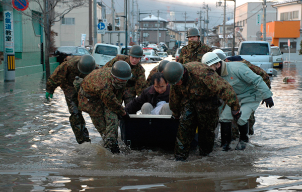 In this Saturday March 12, 2011, photo released by the Japan Defense Ministry, Japanese troopers escort a local resident as they help the evacuation of stranded people at Tagajo, northeastern Japan, after Friday's earthquake and the ensuing tsunami. (AP)