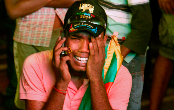 A Sri Lankan cricket fan speaks on the phone and cries after his team lost the World Cup Cricket finals to India, in Colombo, Sri Lanka. (AP)