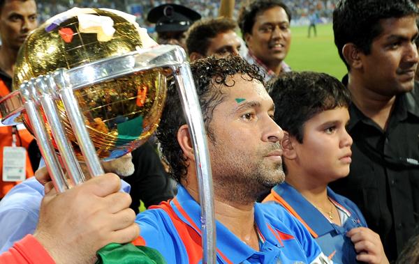 Indian player Sachin Tendulkar (C) holds the trophy as he walks with his son Ramesh (2/R) after India defeated Sri Lanka in the ICC Cricket World Cup 2011 final played at The Wankhede Stadium in Mumbai. (AFP)