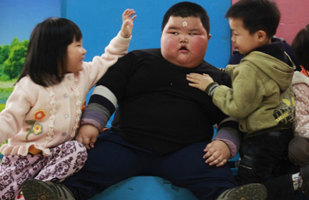 """""""His appetite is so good that for a meal he can eat three big bowls of rice, even larger than I and his mother,"""" his father Lu Yuncheng, who struggles to pick him up, said. (REUTERS)"""