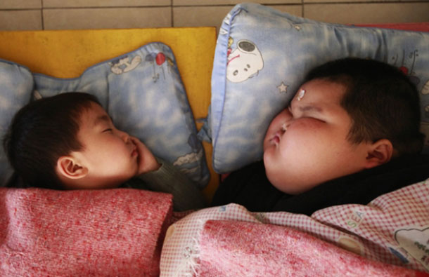 March 29: The toddler takes a nap at a child care center in Foshan, Guangdong province. Last year, his worried parents took him to see specialists at the Guangdong Children's Hospital, where doctors thought his weight gain could be due to a tumor or hormone disorder. (REUTERS)