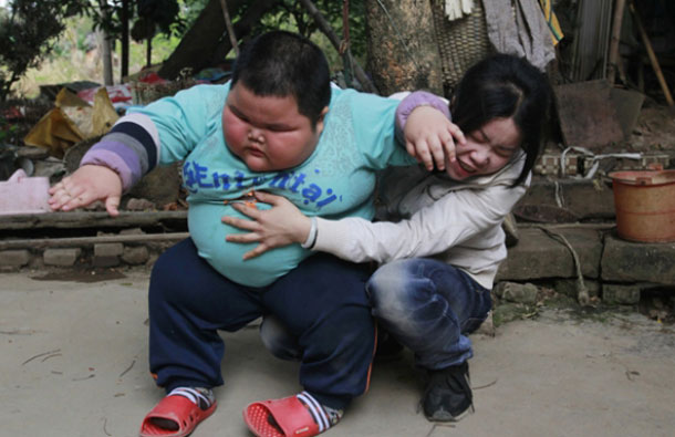 """Lu Hao stands up from his mother's lap outside his house. """"We have to let him be, as if we don't feed him, he will cry nonstop,"""" his mother Chen Huan said. (REUTERS)"""