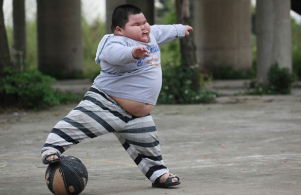 Lu Hao kicks a ball at a basketball court in Foshan, Guangdong province March 28, 2011. Lu, who is 3-feet, 6-inches tall and weighs 132 pounds, put on weight dramatically since his appetite grew when he was 3 months old. (REUTERS)