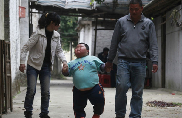 Lu Hao walks with his parents on a street in Foshan, Guangdong province. Ironically, the toddler was underweight when he was born, weighing in at 5.7 pounds, but he started putting on weight at 3 months old and has not stopped. (REUTERS)