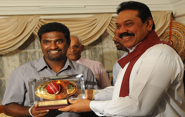 Sri Lankan President Mahinda Rajapakse (R) presents a souvenir to star cricketer Muttiah Muralitharan during a tea party at the official Presidential residency in Colombo. (AFP)