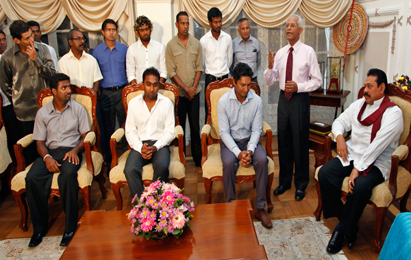 Sri Lankan President Mahinda Rajapaksa, seated right, and the members of Sri Lankan cricket team look on during a meeting at Rajapaksa's residence in Colombo, Sri Lanka. (AP)