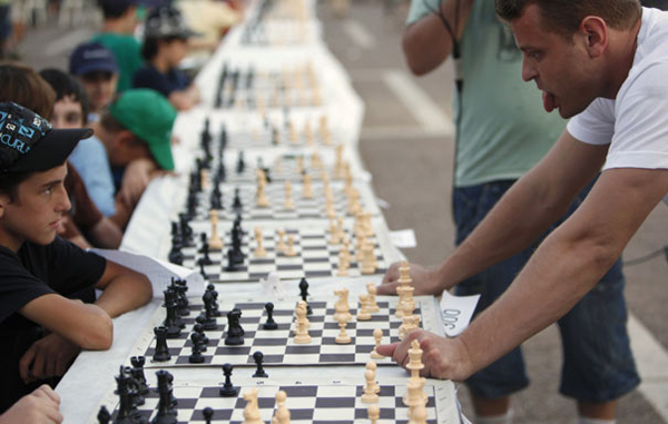 Simultaneous chess game: Israeli grandmaster Alik Gershon (R) looks at a board during a simultaneous chess game at Rabin Square in Tel Aviv October 21, 2010. According to the organisers, Gershon played against 525 opponents on Thursday in an attempt to break the Guinness World Record for simultaneous chess games, currently held by an Iranian. (REUTERS)