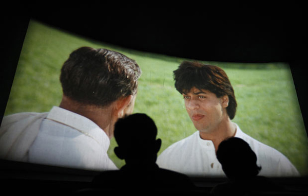 """Completing 770 weeks of continuous screening: Bollywood actor Shah Rukh Khan (R) is seen in the movie screening of """"Dilwale Dulhania Le Jayenge"""" inside Maratha Mandir theatre in Mumbai July 11, 2010. The movie has set a record of completing 770 weeks of continuous screening at a cinema, a feat unmatched by any other Bollywood movie the world over. The movie is screened only in the morning and has special ticket rates which range from $0.30 to $0.40 (15 to 20 Indian rupees). According to Maratha Mandir owner Manoj Desai, the movie, which is still being screened, enjoys at least 60 to 70 percent occupancy on weekdays and a full house on weekends at his theatre. (REUTERS)"""
