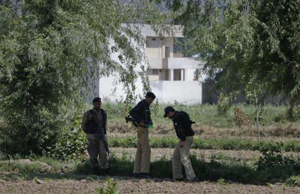 A Pakistani soldier and policemen stand near a compound, where locals reported a firefight took place overnight in Abbotabad, located in Pakistan's Khyber Pakhtunkhwa province, May 2, 2011. (REUTERS)