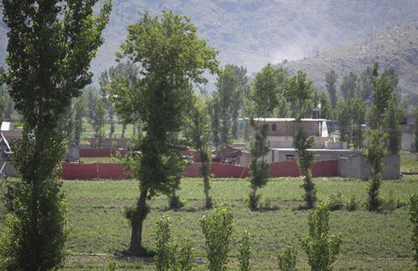 Surrounded in red fabric, a compound is seen where locals reported a firefight took place overnight in Abbotabad, located in Pakistan's Khyber Pakhtunkhwa province, May 2, 2011. (REUTERS)