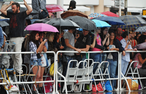 "Fans stand in the rain as they wait for the cast to attend the ""Pirates of the Caribbean: On Stranger Tides"" premiere at the Palais des Festivals during the 64th Cannes Film Festival on May 14, 2011 in Cannes, France. (GETTY/GALLO)"