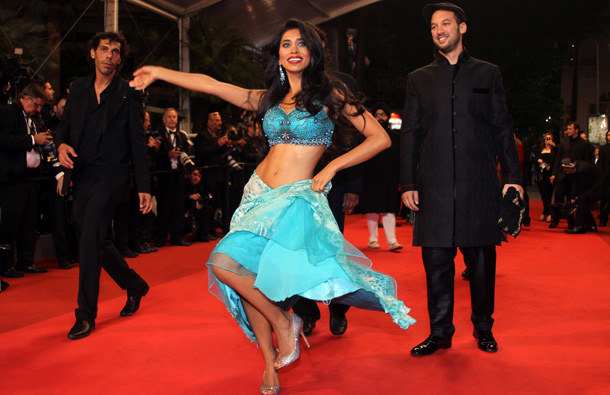 "A dancer dances as US director Jeff Zimbalist arrives on the red carpet before the screening of ""Bollywood - The Greatest Love Story Ever Told"" presented out-of-cometition at the 64th Cannes Film Festival on May 14, 2011 in Cannes. (AFP)"