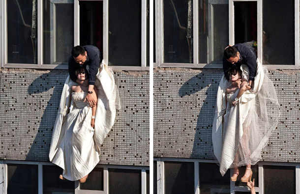 A 22-year-old woman in a wedding gown is grabbed by Guo Zhongfan, a local community officer, as she attempts to kill herself by jumping out of a seven-storey residential building in Changchun, Jilin province. (REUTERS)