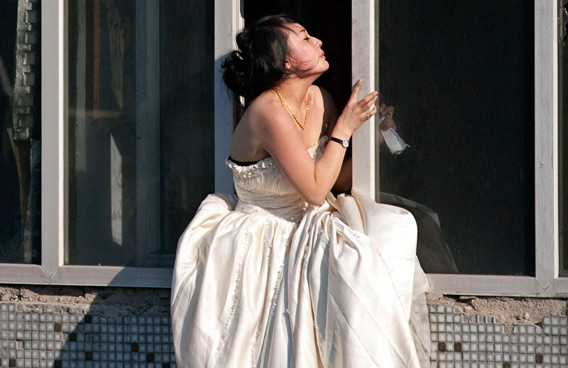 A 22-year-old woman in a wedding gown sits on a windowsill before attempting to kill herself by jumping out of a seven-storey residential building in Changchun, Jilin province. (REUTERS)