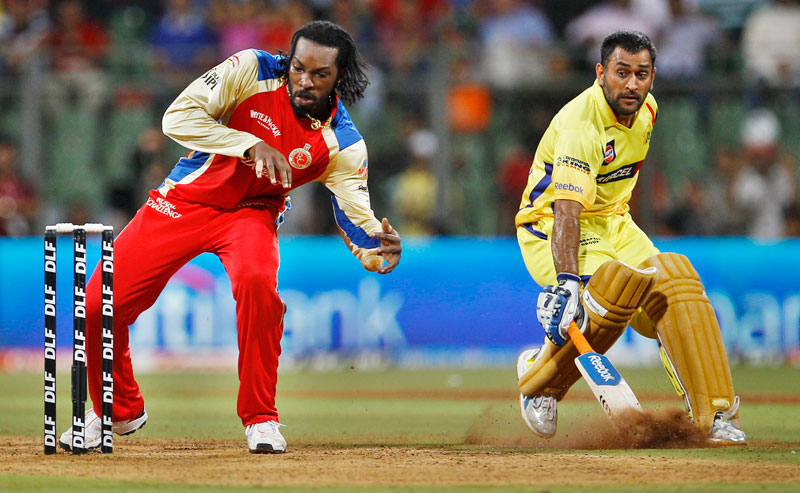 Royal Challengers Bangalore's Chris Gayle, left, makes an attempt to run out Chennai Super Kings' captain Mahendra Singh Dhoni, right, during their Indian Premier League (IPL) Qualifier 1 cricket match in Mumbai, India. (AP)