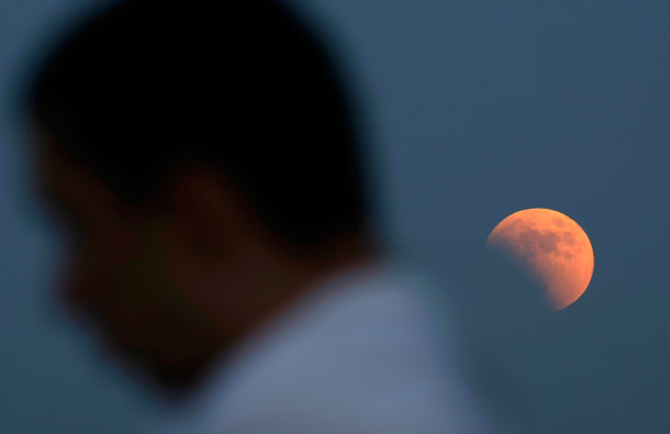 A man walks by as a partially eclipsed moon rises on the sky over Belgrade Serbia. The total lunar eclipse was visible throughout most parts of Europe on Wednesday evening. (AP)