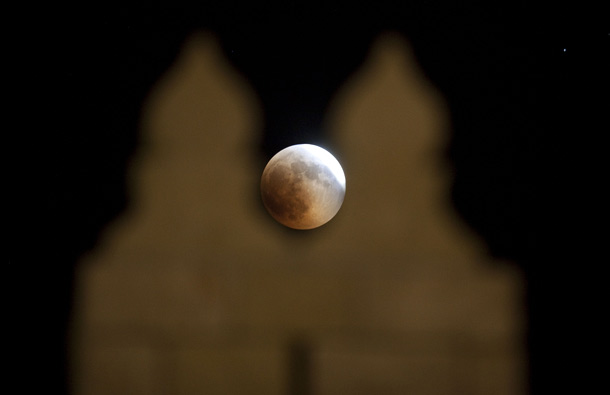 A total lunar eclipse is seen through the old city walls in Jerusalem, Israel. The longest lunar eclipse for a decade took place tonight. A lunar eclipse comes when the sun, Earth and moon line up and Earth's shadow falls on the moon. (GETTY/GALLO)
