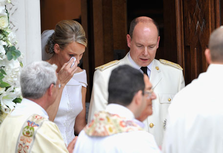 Princess Charlene of Monaco wipes away a tear as she and Prince Albert II of Monaco leave Sainte Devote church after their religious wedding ceremony at the Prince's Palace of Monaco on July 2, 2011 in Monaco. The Roman-Catholic ceremony followed the civil wedding which was held in the Throne Room of the Prince's Palace of Monaco on July 1. With her marriage to the head of state of the Principality of Monaco, Charlene Wittstock has become Princess consort of Monaco and gains the title, Princess Charlene of Monaco. Celebrations including concerts and firework displays are being held across several days, attended by a guest list of global celebrities and heads of state. (GETTY IMAGES)