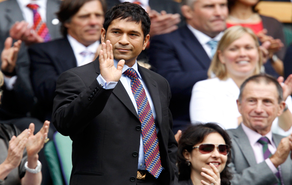 Cricket player Sachin Tendulkar, waves as he arrives on Centre Court for the match between Caroline Wozniacki of Denmark and Jarmila Gajdosova of Australia at the Wimbledon tennis championships in London. (REUTERS)