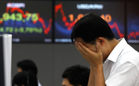 A foreign currency dealer of the Korea Exchange Bank rubs his face as he works in front of a screen (L) displaying the Korea Composite Stock Price Index (KOSPI), at the bank's dealing room in Seoul. (REUTERS)