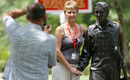 Michael Winwood of South Hampton England gets a photo of his wife, Dianne,  during Elvis Fan Appreciation Day at the Elvis Presley Birthplace Wednesday, Aug 10, 2011  in Tupelo Miss.  (AP)