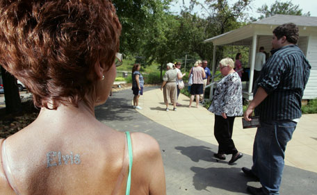 """With """"Elvis"""" stamped on her back, Gaynor Gregory, of South Wales, waits her turn to make a tour through the Elvis Presley Birthplace during Elvis Fan Appreciation Day in Tupelo Miss. Wednesday, Aug 10, 2011. (AP)"""