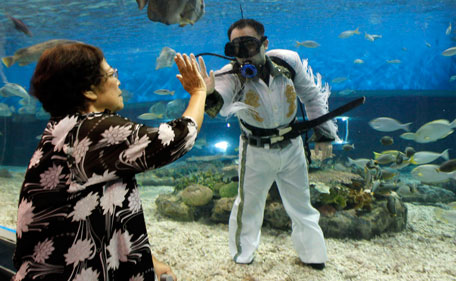 """A visitor gives a high five to a professional diver wearing an Elvis Presley attire inside an aquarium of the Ocean Park in Manila August 15, 2011. Presley, the """"King of Rock and Roll"""", died at his home, Graceland Mansion, in Memphis, Tennessee, at the age of 42 on August 16, 1977 from drug overdose. (REUTERS)"""
