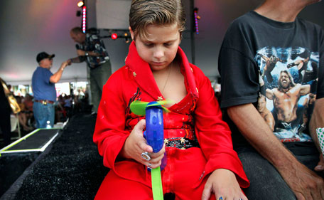 Brandon Bird, 9, tries to keep cool in his self-designed jumpsuit during a series of performances by Elvis tribute artists at the Graceland Entertainment Pavilion in Memphis, Tenn, before a vigil marking the 34th anniversary of the death of Elvis Presley Monday night, Aug. 15, 2011. (AP)