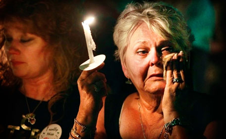 """Charlotte Stone of Griffin, Ga., wipes tears from her eyes as the song """"Can't Help Falling In Love"""" is played during a candlelight vigil marking the 34th anniversary of the death of Elvis Presley, Monday, Aug 15, 2011 at Graceland in Memphis, Tenn. (AP)"""