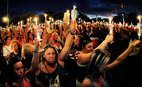 Elvis fans from all over the world gather at the gates of Graceland for a candlelight vigil marking the 34th anniversary of the death of Elvis Presley, Monday, Aug 15, 2011 in Memphis, Tenn. (AP)